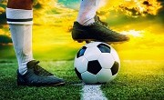 feet of football player tread on soccer ball