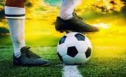 feet of football player tread on soccer ball